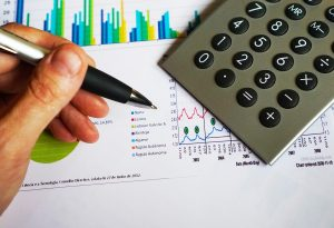 imagem com uma calculadora prata, a mão de um homem segurando uma caneta e um papel com gráficos coloridos atrás.