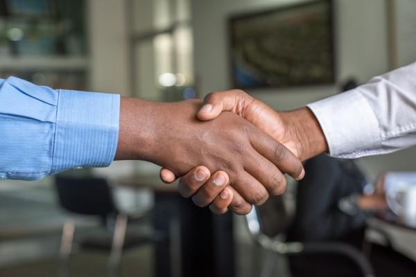 Duas pessoas dando um aperto de mão exemplificando a responsabilidade social corporativa